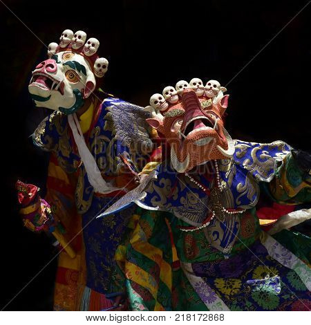Buddhist monks in ritual tantric costumes bright colors and ancient masks on black background.