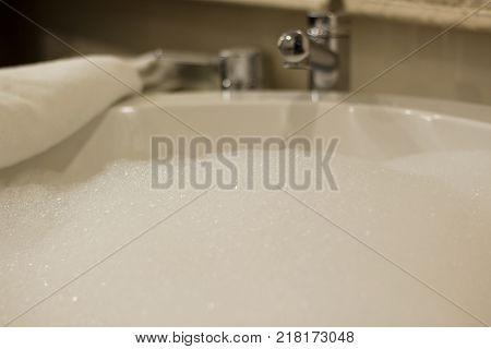 Bubble bath foam in a white bath tub with a white towel.