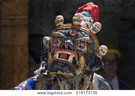 Ancient ritual Buddhist mask Palden Lhamo, blue, red eyes and mouth, huge white fangs, skulls on the top of the mask.