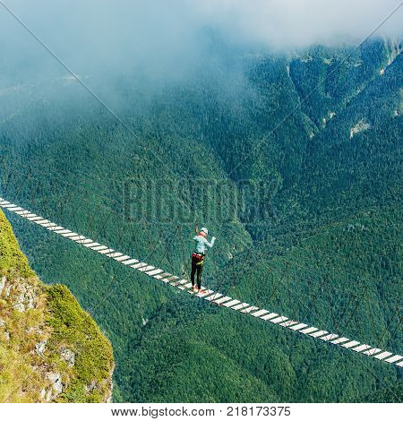 Woman crossing the abyss on the rope bridge.
