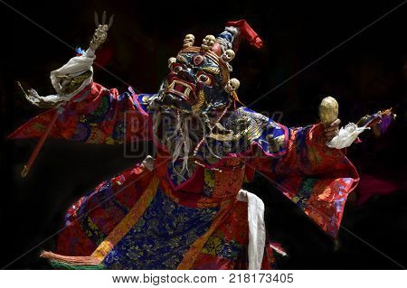 Performance of the traditional Tibetan Mask Dance, the figure of Palden Lhamo on a black background, the Himalayas, India.