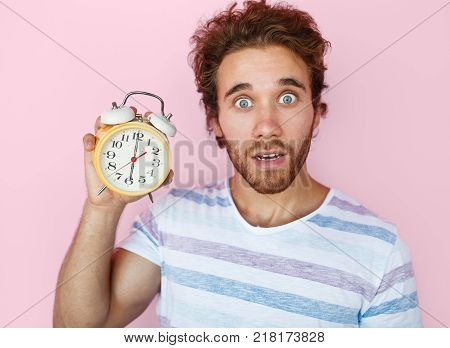 Young terrified man holding clock and looking expressively at camera.