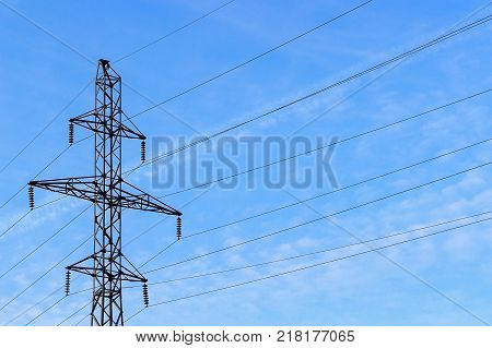 Metal support (elektroopora) of overhead power lines against a blue sky with clouds.