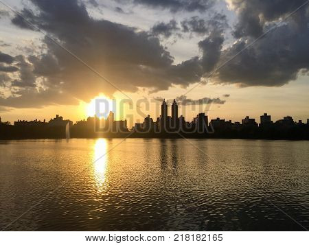Silhouette Buildings in Manhattan and cloudy sunset sky over lake at Jacqueline Kennedy Onassis Reservoir