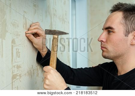 A Man Hammers A Nail Into Plaster Wall Under The Wallpaper