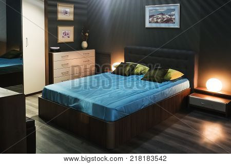 Stylish modern bedroom design with double bed wardrobe bedside table chest of drawers and lamps Blue sheets on the bed. a room in an expensive hotel