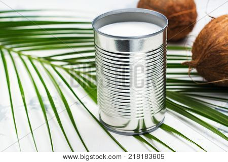 Opened tin can with coconut milk drink. Alternative non dairy vegan milk on white stone table