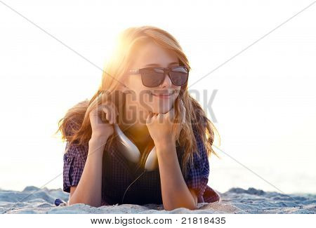 Beautiful girl with headphones at the beach in sunrise time.