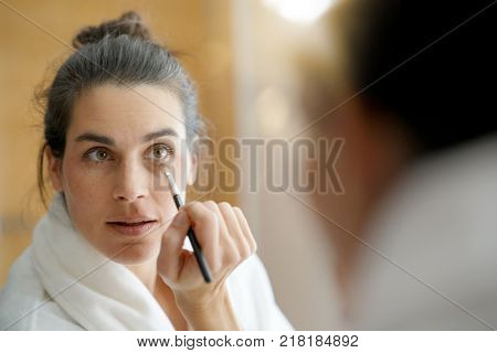 Woman in front of mirror putting makeup on