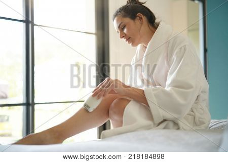 Woman in bedoom shaving legs with electric razor