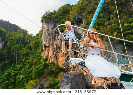 Happy family aboard. Young mother little baby boy on board of sailing yacht. Child have fun discovering tropical islands in summer cruise. Travel adventure yachting with kids on family vacation.