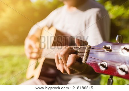 Man fingers playing guitar outdoor in summer park. Musician man and her guitar in nature park Practice guitar.