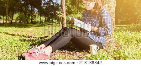 The girl sitting on a green grass with cup of coffee and reads the book young woman with coffee sitting on the grass and reading a book in the park banner panoramic crop for copy space. asian woman reading book in Thailand. asian Beautiful woman reading a