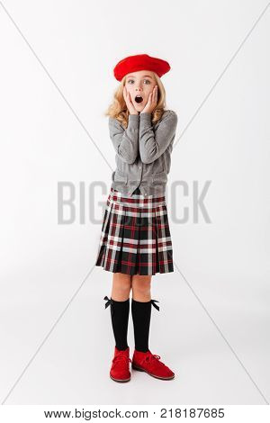 Full length portrait of a shocked little schoolgirl dressed in uniform standing and looking at camera with open mouth isolated over white background