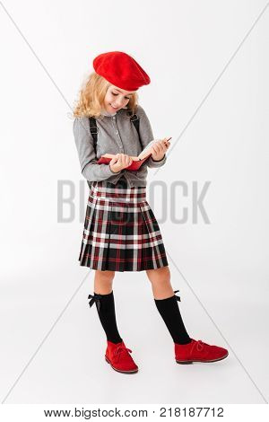 Full length portrait of a lovely little schoolgirl dressed in uniform with backpack reading book while standing isolated over white background