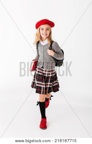 Full length portrait of a cheerful little schoolgirl dressed in uniform with backpack holding book while running and looking at camera isolated over white background