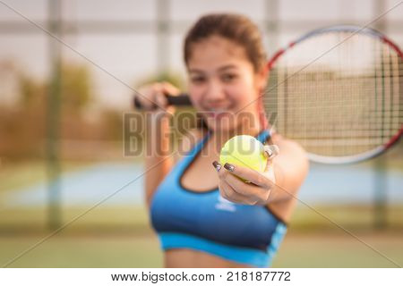 Woman hand holding tennis ball and racket in court. tennis ball on hand. tennis ball on sunset. tennis sport girl. tennis ball and racket. tennis player