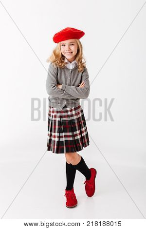 Full length portrait of a happy little schoolgirl dressed in uniform standing with arms folded isolated over white background