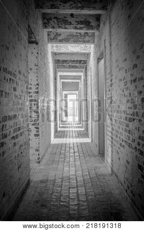 Light At The End Of The Tunnel. Long brick hallway with bright light shining through the open door at the end.