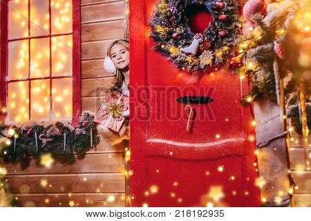 Beautiful child girl peeking out of the door of her house decorated for Christmas and holding a gift. Time for miracles.