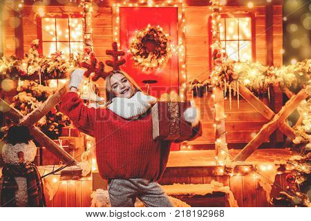 Pretty child girl is standing on the porch of a house decorated for Christmas and holding a gift. Time for miracles.