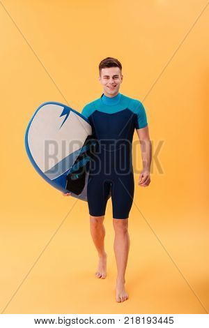 Full lenth photo of cheerful guy in swimsuit holding surfboard while walking and looking at camera, isolated on yellow background