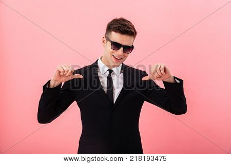 Young handsome man in official suit and sunglasses pointing at himself isolated over pink