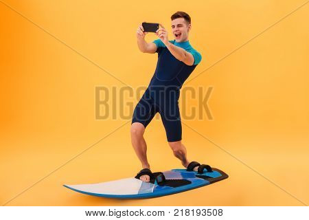 Full length photo of young smiling man in swimsuit taking selfie on smartphone while surfing on surfboard, isolated over yellow background
