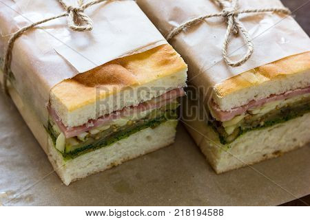 Piece of sandwich ham cheese with lettuce and tomato on wood plate. Homemade sandwich served with orange juice for breakfast or lunch. Delicious ham cheese sandwich ready to served on wood table. Triangle slice sandwich ham and cheese.