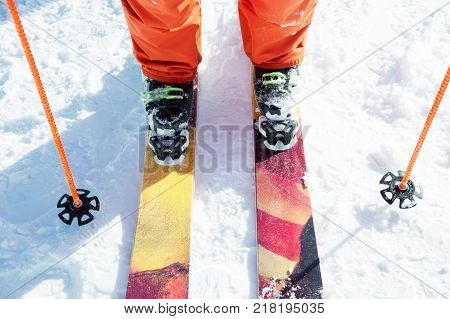 Legs athlete skier in an orange overall on a skiing ski next to ski poles in the snow on a sunny day. The concept of winter sports