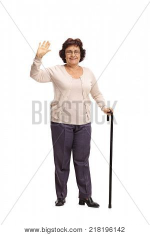 Full length portrait of an elderly woman with a cane waving at the camera isolated on white background