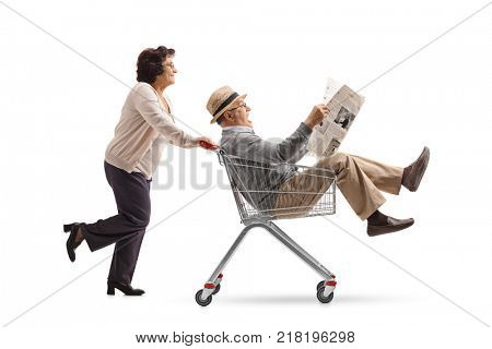 Elderly woman pushing a shopping cart with a mature man riding inside and reading a newspaper isolated on white background