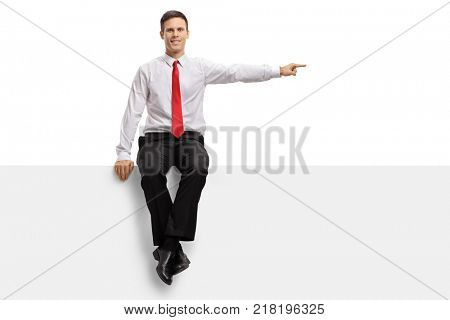 Formally dressed guy sitting on a panel and pointing isolated on white background