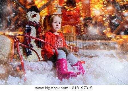Cute three year old girl sits on the sled in the yard of her house decorated for Christmas.Time for miracles. Merry Christmas and Happy New Year.