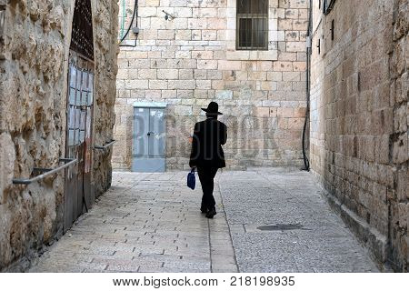 One unrecognized religious jewish man walking down the street in Old City of Jerusalem.