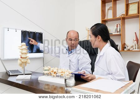 Chiropractors analyzing spine x-ray on the wall