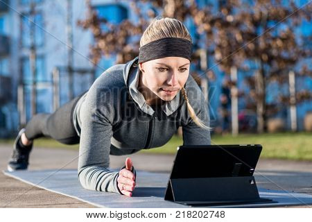 High-angle view of a fit young woman, watching a motivational video on tablet PC while exercising the forearm plank position on a mat outdoors in the park
