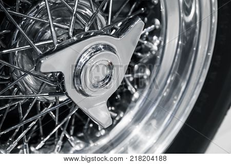 Chromed wheel disc. Luxury Italian vintage sport car fragment close up photo with selective soft focus
