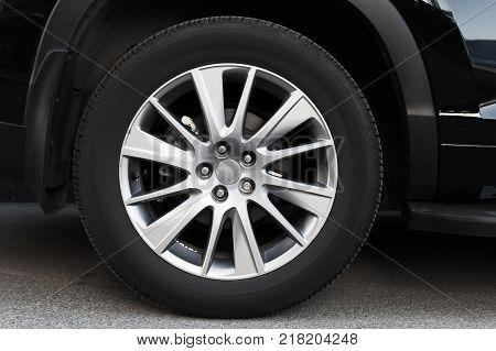 Modern automotive wheel on light alloy disc close up photo