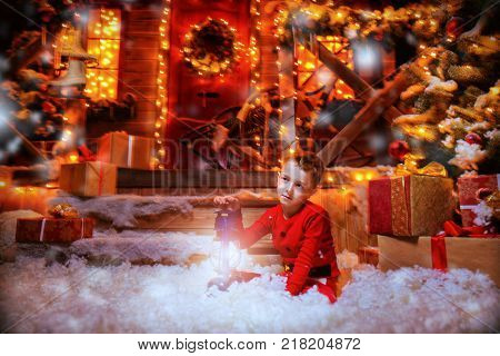 Cute child boy is sitting near his house decorated for Christmas and holding a lantern. Time for miracles. Merry Christmas and Happy New Year.