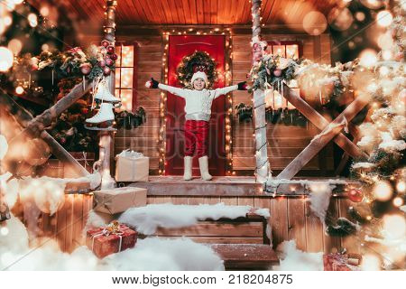 Cute child boy stands on the porch of the magic house of Santa Claus. Miracle time. Merry Christmas and Happy New Year.