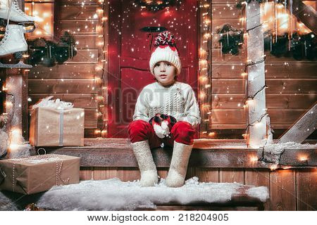 Cute child boy sits on the porch of the magic house of Santa Claus. Miracle time. Merry Christmas and Happy New Year.