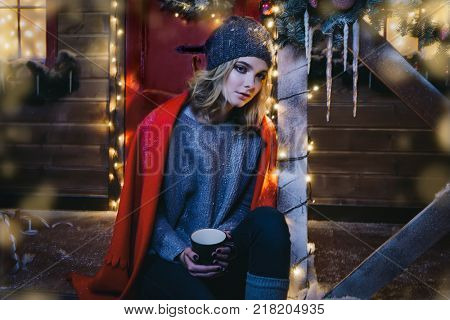 Pretty girl is sitting on the porch of a house decorated for Christmas and holding a cup of tea. Time for miracles.