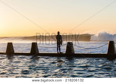 Surfing surfer Body Boarder unidentified on tidal pool wall waiting jump moment into ocean waves overlooking action photo.