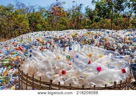 Ban Khok Thailand - February 3 2017: used plastic bottles stored in a landfill between tree area. the bottles will be clean and melted to create new plastic.