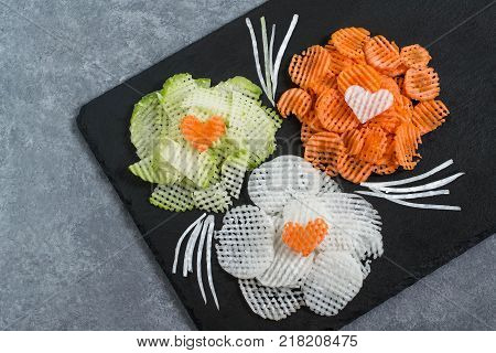 Figured slicing vegetables for vitamin salad. Flowers from carrot daikon and radishes on slate plate. Detox product. Vegetarian healthy and diet food. Culinary improvisation on Valentine's Day theme