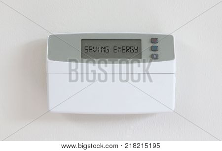 Vintage digital thermostat hanging on a white wall - Covert in dust - Saving energy poster