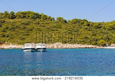 Two yachts anchored side by side in the beautiful Milne Bay - Hvar, Croatia