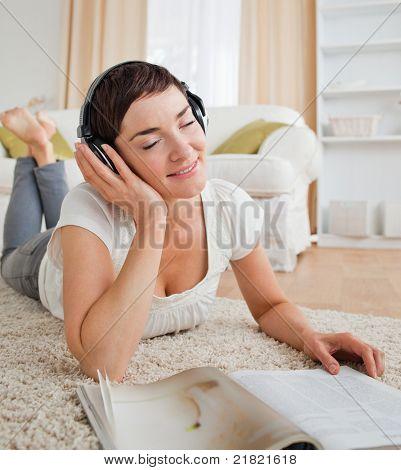 Porträt einer erfreut Frau mit einem Magazin einige Musik genießen