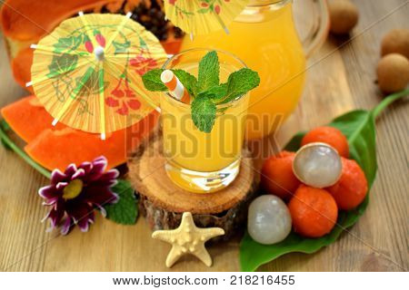 Yellow beverage decorated with mint, straws and little cocktail umbrellas in glass vessels surrounded by tropical fruits on a wooden table